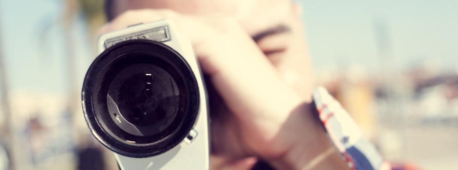 Junge filmt mit einer Super-8-Kamera