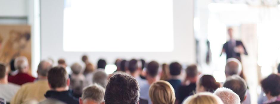 Menschen hören bei einem Vortrag zu