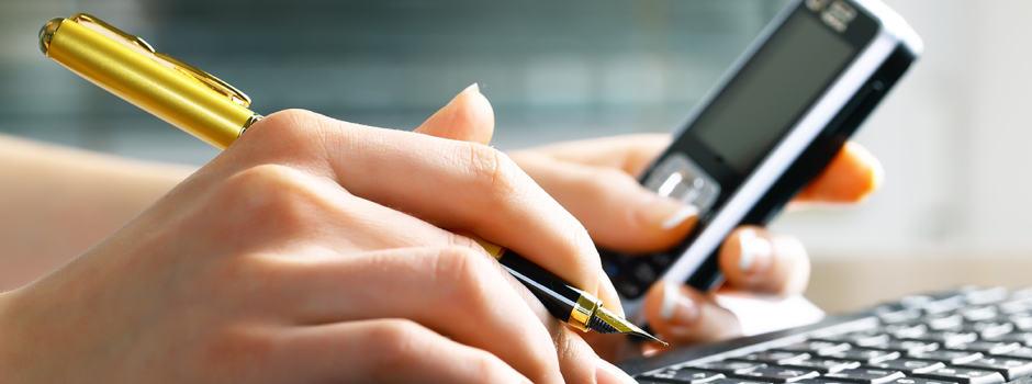 Hand mit Stift und Handy auf der Tastatur