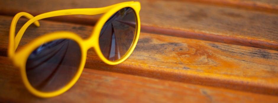 Gelbe Sonnenbrille auf Holz