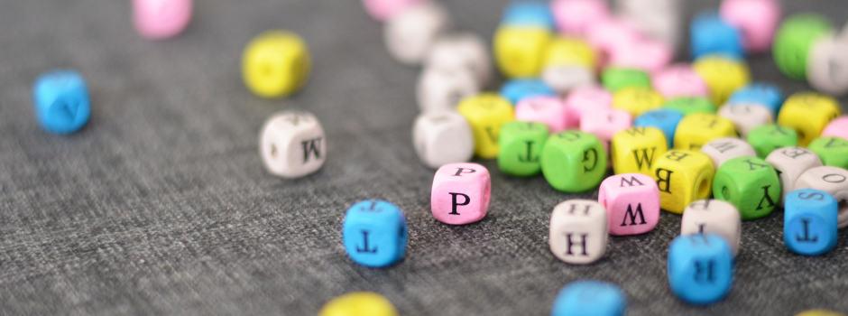 Bunte Buchstabenwürfel auf grauem Stoff