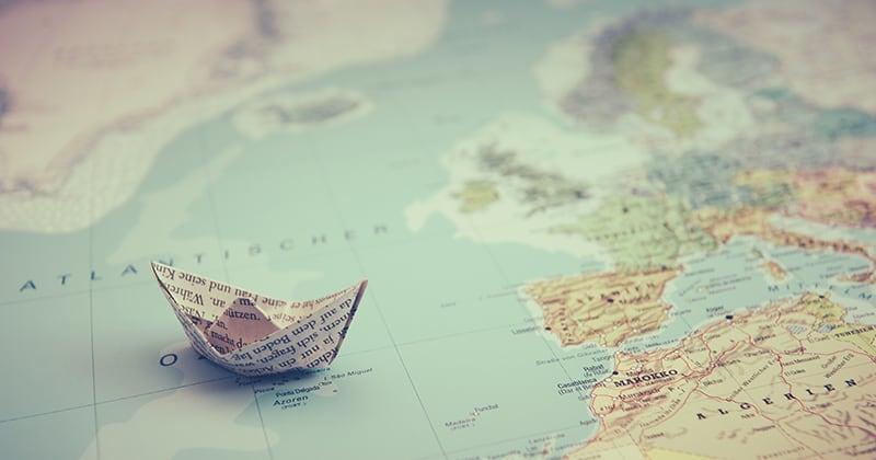 Customer Journey als Papierboot auf der Weltkarte